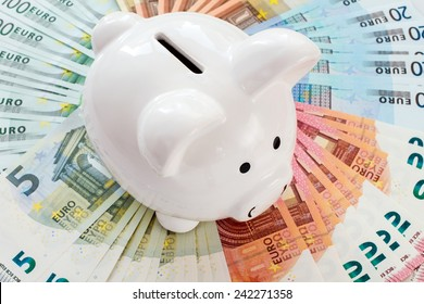 White piggy bank surrounded by Euro notes