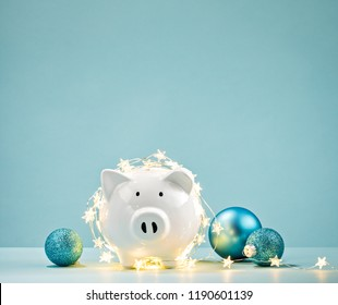 White Piggy bank wrapped in a string of Christmas lights over a blue background. Saving concept.