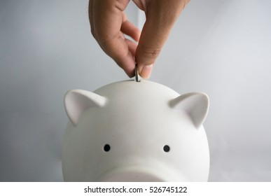 White piggy for money saving with coin and hand