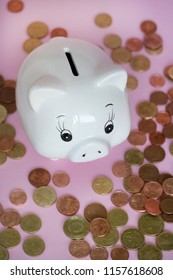 white piggybank with heap of coins on pink background