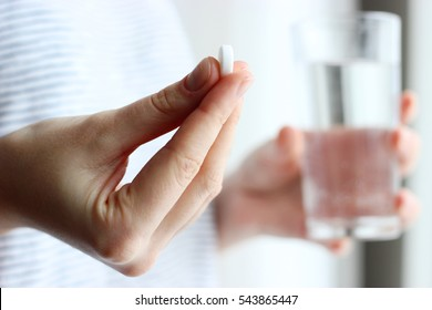 white pill and a glass of water in female hands. health concept
