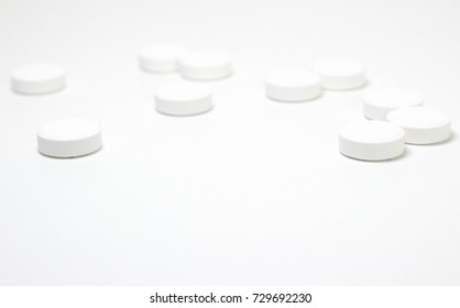 White pill and tablets, medicine isolated.  Medical background.