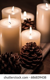 white pillar candles and pine cones