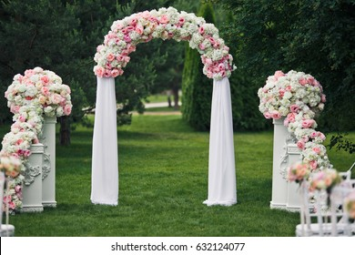 White pillars and arch decorated with pink and white peonies