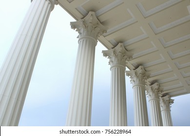 white pillars with cloudy sky
