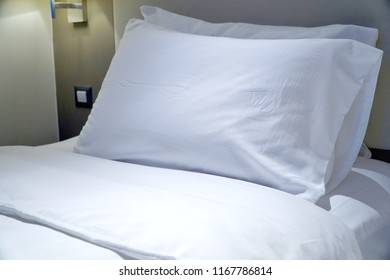 White pillow and bed sheets in room at the hotel. Soft and comfortable. Good sleep. Free space for any text.