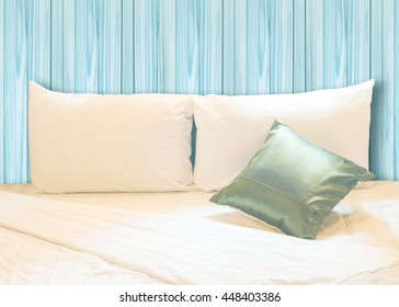 white pillow and green pillow on bed and with wrinkle messy blanket in vintage wooden bedroom, from sleeping in a long night.