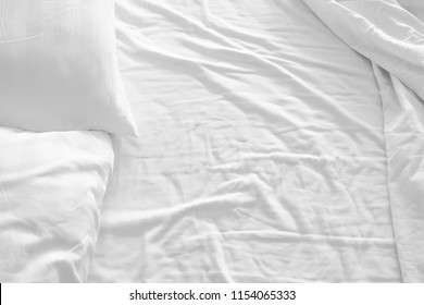 white pillow with messy messy blanket on bed in bedroom Close up of bedding sheets with copy space