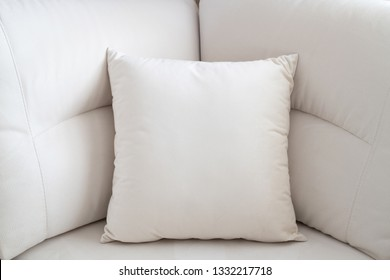 The White pillow on the light sofa