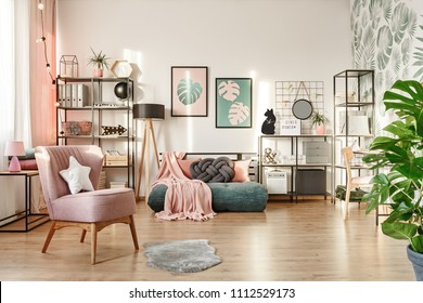 White pillow on pink armchair in cozy bedroom interior with blanket on green mattress