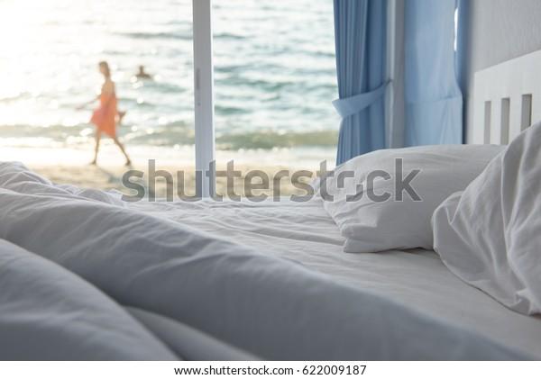 Белые подушки и постельные принадлежности в чистой спальне отеля с женщиной, идущей по пляжу, фон с видом на море, счастливый летний отдых на роскошном курорте
