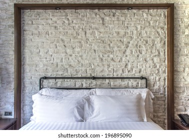 white pillows on a classic bedroom with white brick wall in background