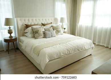 white pillows setting on bed with English country style bedding decoration and side table lamp