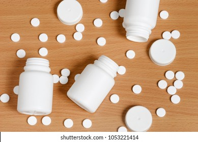 White pills and bottles scattered on flat polished wooden surface and going out of frame. Pills and bottles are white. Bottles are opened. Covers lay nearby.