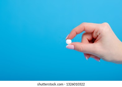 White pills in hand pharmasy medecine on blue background