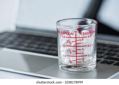 white pills in measuring cup on laptop computer background.