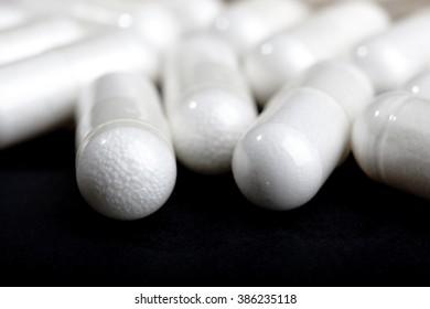 white pills on black