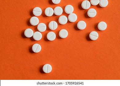 white pills on orange background. drugs isolated orange copy space. healthcare medicine concept, aspirin, antibiotics