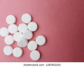 White pills on pink background.