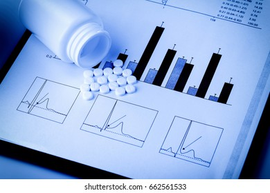 white pills and printed medical graphs in blue tone