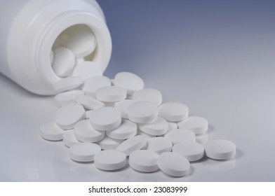 White pills spilling out of white bottle