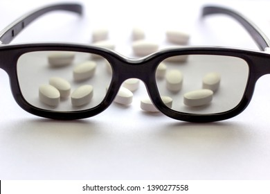 White pills and tablets with glasses on light background. Pharmacy and medicine concept. Focused on a pharmaceutical industry for eye diseases. Selective focus photography