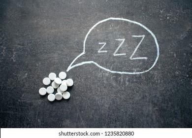 White pills in Z shape and text. Sleeping pills, hypnotic drugs, sedative, melatonin on dark night background