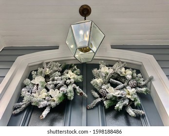 White pine and pine cone wreaths on a blue front door with a pendant light decorate a porch for the winter holidays.