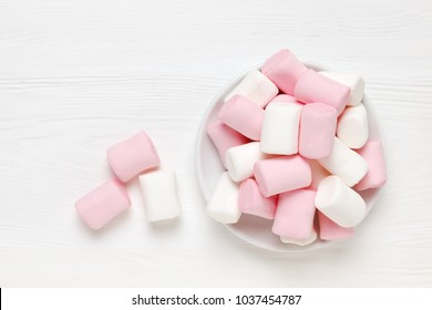 White and pink marshmallow on a saucer on a white wooden surface. pink mood.Top view