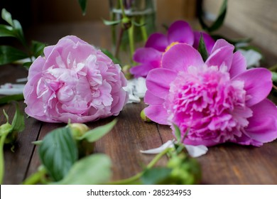 white and pink peonies bouquet from flowers market on a dark wood table in rustic style