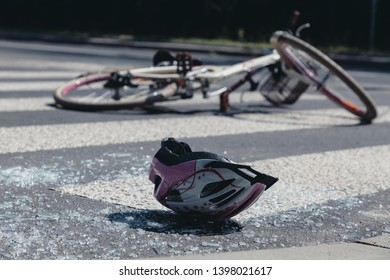 White and pink teenage girl's helmet lying on broken glass after terrible car crash