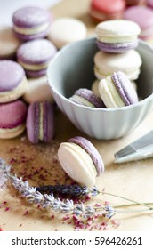 White, pink, violet and lavender colored macaroons with lime and lavender cream dusted with powder sugar and lavender flowers.