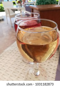 White and pink wine in glasses on a table of rattan