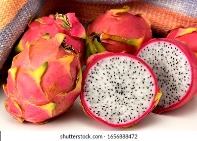 The white pitaya or dragon fruit sliced on a white board and a rustic fabric at the background
