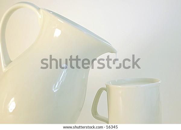 White pitcher pouring milk into a white mug