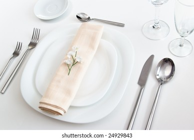 white place setting with white plates forks glasses beige napkin and little flower