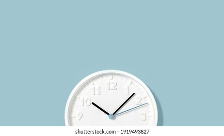 White plain analogue wall clock on trendy pastel blue background. Five past ten oclock. Close up with copy space, time management concept and opening or closing time