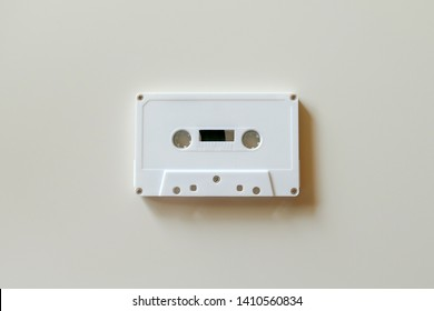 a white and plain cassette tape on a white table