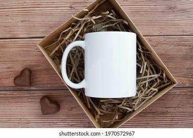 White plain coffee mug mockup in gift box, rustic dark wood background, heart shape chocolate candies, Valentines day gift.