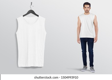 White plan sleeveless shirt on a man male model in black denim jeans pant, isolated, mockup. Hanging white blank sleeveless shirt shirt, against empty wall.