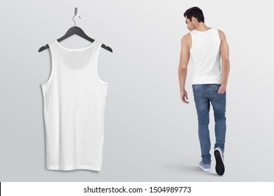 White plan tank top shirt on a man in blue denim jeans pant, isolated, mockup. Hanging white blank tank top shirt, against empty wall.