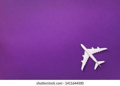 White plane, airplane on violet color background with copy space. Top view, flat lay. Minimal style design. Travel, vacation concept.