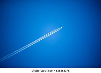 White plane flying high in blue sky