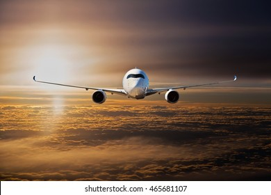 White plane flying at sunset time above the clouds. Aircraft front view.