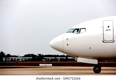 A white plane is taxiing to the gate.