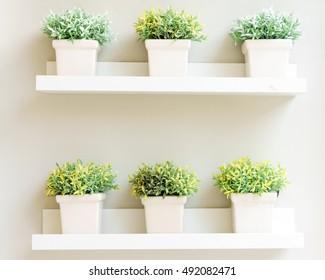 white plant bucket on wall shelf interior decorative