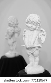 White plaster figurine Angel Cupid on a light background with reflection.