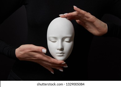 White plaster mask face is holding woman's fingers on a black background, copy space. Concept social psychological masks