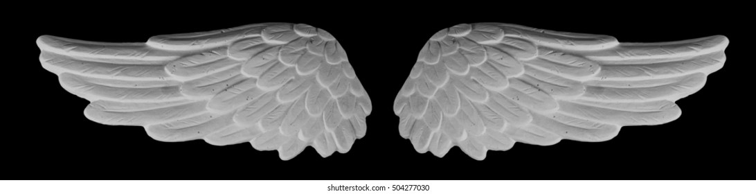 White plaster wings on isolated black background