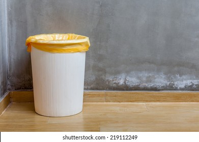The white plastic bin with orange bag on wooden floor with exposed cement background, for cleaning and recycle.